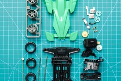 Flatlay mini 4WD toy cara awaiting to be assemble on cutting mat. Popular toy car during 90's.