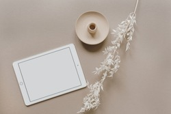 Flatlay of blank screen tablet pad, white floral branch, decorations on neutral pastel beige background. Home office desk workspace. Business, work template. Flat lay, top view.