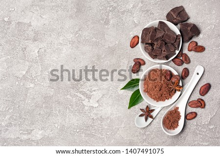 Flatlay of chocolate chunks with cocoa beans and powder for confectionery on gray concrete background with copy space