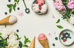 Flatlay of pink strawberry and coconut ice cream scoops, sweet cones and peony flowers bouquet over white background, top view, copy space. Summer food concept