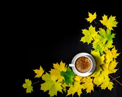 flatlay on a black background are yellow juicy bright autumn maple leaves in the form of a corner frame and they have a white cup with coffee