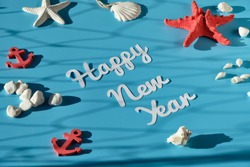 flatlay: The words 'Happy New Year' are written with white letters on blue background. Paper flatlay with shallow depth of fields, symbols of the sea like shells, starfish and anchor decorate the scen