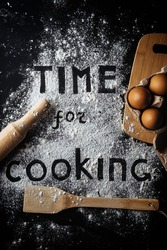 flatlay with baking tools and eggs on a black table. Time for cooking text made with flour. Food typography concept. copy space.