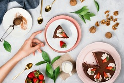 Flatlay with woman's hand reaching for a piece of vegan chocolate cake surrounded by walnuts, strawberries, cocoa powder and other dessert ingredients on cement background