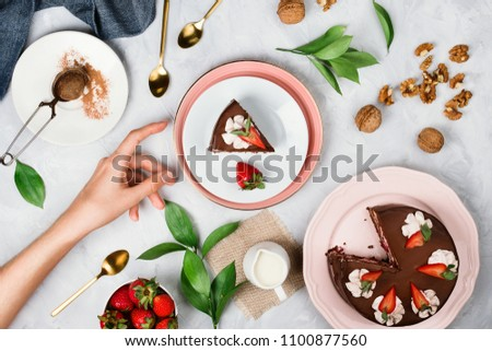 Flatlay with woman's hand reaching for a piece of vegan chocolate cake surrounded by walnuts, strawberries, cocoa powder and other dessert ingredients on cement background #1100877560