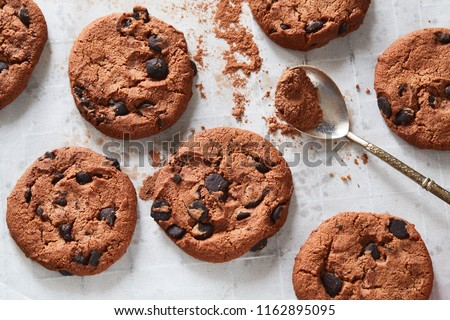 Flatview of handcrafted chocolate cookies with chocolate chips and tea spoon with cocoa powder on baking paper. Natural handmade organic snakes for healthy breakfast