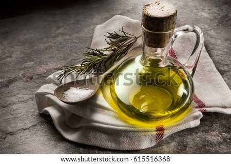 Flavored olive oil with rosemary and pepper on stone and wooden table