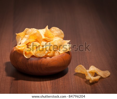 Flavored potato crisps in wooden bowl on table
