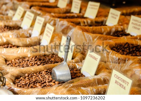 flavoured coffee beans in hessian bags at a market stall #1097236202
