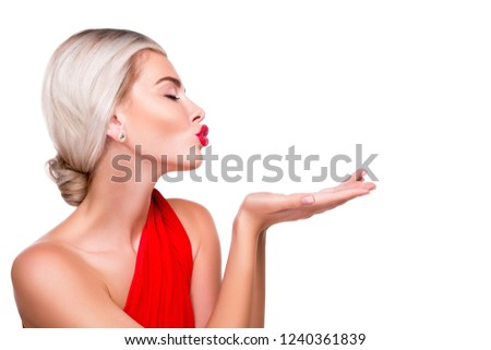 flawless model in the profile makes an air kiss over his empty hand, a place for an advertising slogan or product. isolated. White background. beautiful caucasian girl in red dress with red lips. kiss