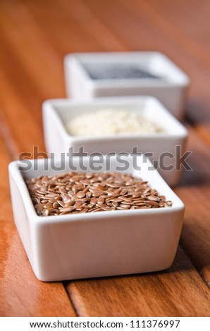 Flax, poppy and sesame seeds in little bowls.
