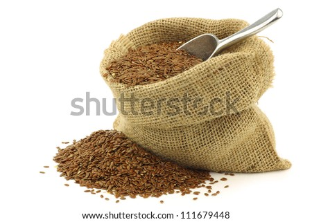 Flax seed (linseed) in a burlap bag with an aluminum scoop on a white background