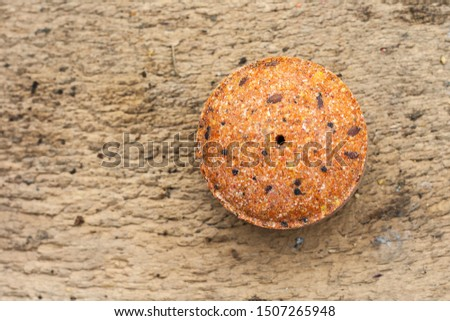 Flax seeds pressed into a round briquette. It is used as feed for animals, birds and fish. One of the feed ingredients. Copy space.