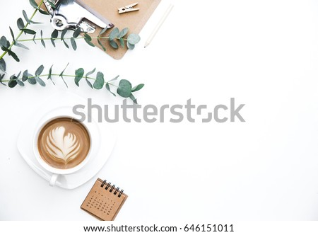 Flay lay, Top view office table desk. Feminine desk workspace frame with green leaves eucalyptus, clipboard and coffee  on white background.  ideas, notes or plan writing concept