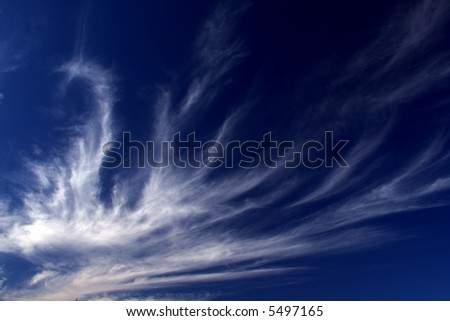 Fleecy clouds on the dark-blue sky background 2