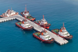 Fleet of tug boats moored in a port. Aerial view