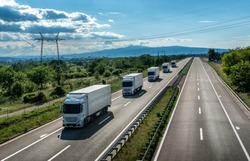 Fleet or Convoy of big transportation trucks in line  on a countryside highway under a blue sky