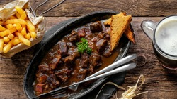 flemish stew with french fries, gingerbread and brown beer on wooden table