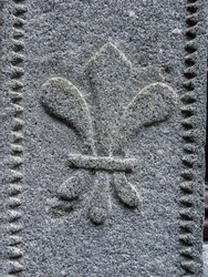 Fleur-de-lis (fleur-de-lys) stylized lily and decorative motif used in French heraldry carved on gray stone and 17th century architectural element in Lourdes castle, Hautes-Pyrenees, South France