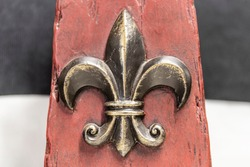 Fleur-de-lis on red wood and black and white background.