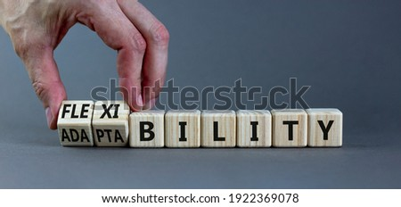 Flexibility and adaptability symbol. Businessman turns wooden cubes and changes words 'adaptability' to 'flexibility'. Grey background, copy space. Business, flexibility and adaptability concept. Foto stock ©
