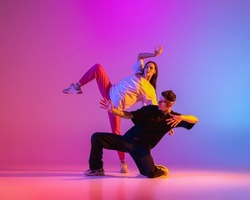 Flexibility and grace. Two young people, guy and girl, dancing contemporary dance over pink background in neon light. Modern dance aesthetics concept