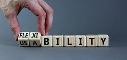 Flexibility and usability symbol. Businessman turns wooden cubes and changes words 'usability' to 'flexibility'. Beautiful grey background, copy space. Business, flexibility and usability concept.