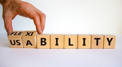 Flexibility and usability symbol. Businessman turns wooden cubes and changes words 'usability' to 'flexibility'. Beautiful white background, copy space. Business, flexibility and usability concept.