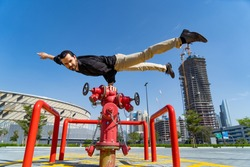 Flexible Acrobat keep balance with one hand on the fireman hydrant with blurred Dubai cityscape. Concept of modern and safety
