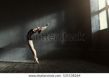 Flexible ballet dancer stretching in the dark lighted studio