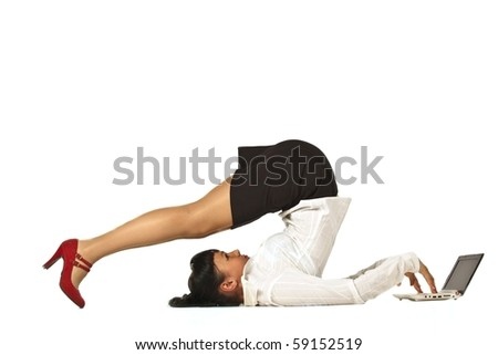 Flexible businesswoman with laptop computer over white background - stock photo