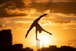 Flexible female circus Artis keep balance on one hand on the rooftop against dramatic sunset and cityscape. Handstand and equilibrium concept