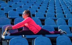 Flexible girl child in sportswear do splits stretching legs on stadium seats, flexibility