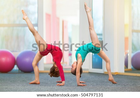 Flexible kids gymnasts doing acrobatic exercise in gym. Sport, training, fitness, yoga, active lifestyle concept