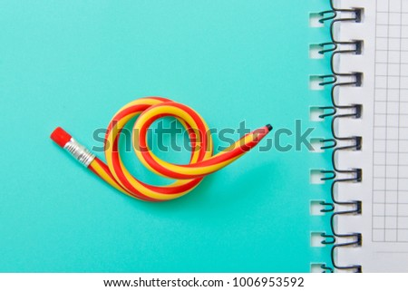 Flexible pencil on a turquoise notebook. Bent pencils two-color