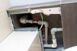 flexible plastic pipe in the hatch in the ceiling. replacement of the riser and pipes through the tiles cut in the ceiling. Red ball valve on a Pex-Al-Pex pipe with union nut, sleeve nut in a