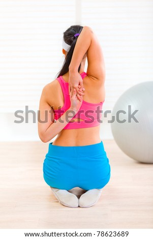 Flexible slim woman doing gymnastics exercise at living room