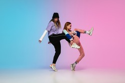 Flexible. Sportive girls dancing hip-hop in stylish clothes on colorful gradient background at dance hall in neon light. Youth culture, movement, style and fashion, action. Fashionable portrait.