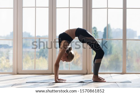 Flexible sporty girl stretching at gymnastic studio over big panoramic window, copy space