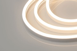 Flexible warm white led neon decor light glowing on dark background.