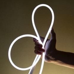 Flexible white led tape neon in hand on black background.