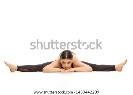 Flexible young woman doing yoga side leg splits on white background