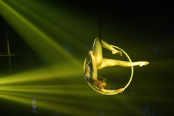 Flexible young woman make performance on aerial hoop, flexible back on aerial hoop, aerial circus show, yellow light. Flexible woman gymnast upside down on hoop