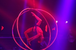Flexible young woman make performance on aerial hoop, flexible back on aerial hoop, aerial circus show, blue and red light. Flexible woman gymnast upside down on hoop. Night club performance