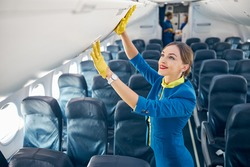 Flight attendant in blue suit and yellow lather gloves checking compartment with hand luggage while standing in the empty board of commercial airplane