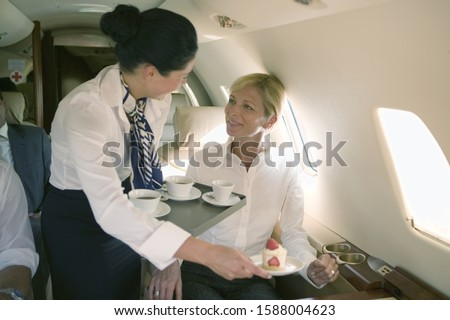 Flight attendant offering coffee to businesswoman on airplane