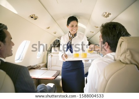 Flight attendant offering juice to businessman on airplane