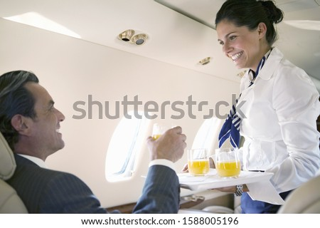 Flight attendant offering juice to businessman on airplane Photo stock ©