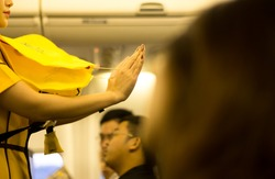 Flight attendant presenting a life vest on board before the flight departure
