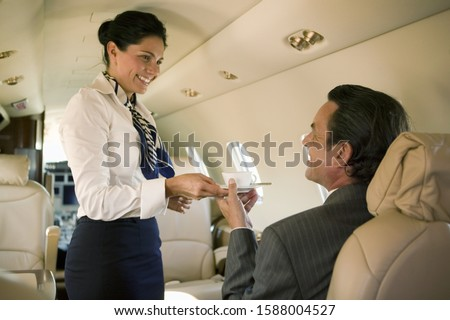 Flight attendant serving drink to businessman on airplane